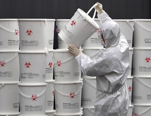 A worker in protective gear stacks plastic buckets containing medical waste from coronavirus patients at a medical center in Daegu, South Korea, Monday, Feb. 24, 2020. (Lee Moo-ryul/Newsis via AP)