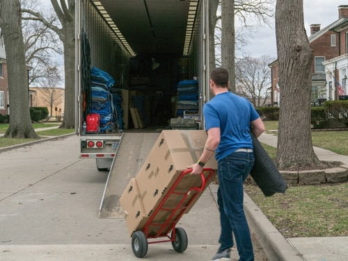 A moving company employee loads a moving truck with a service member's household goods during the permanent change of station peak-season at Scott Air Force Base, Ill., March 7, 2018. (Air Force Staff Sgt. Oz Suguitan/TRANSCOM)