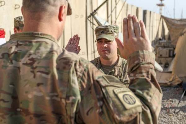 Lt. Col. John Hawbaker, commander of the 1st Squadron, 73rd Cavalry Regiment, 2nd Brigade Combat Team, 82nd Airborne Division, issues the oath of re-enlistment to Sgt. Patrick Bradford, an infantryman, at Qayyarah West, Iraq, Jan. 26, 2017. (Staff Sgt. Jason Hull/Army)