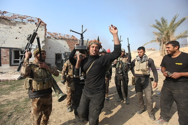 RAMADI, IRAQ - DECEMBER 28: Members of the Iraqi security forces celebrate after retaking Ramadi city from Daesh, in Ramadi, Iraq on December 28, 2015. (Photo by Ali Mohammed/Anadolu Agency/Getty Images)