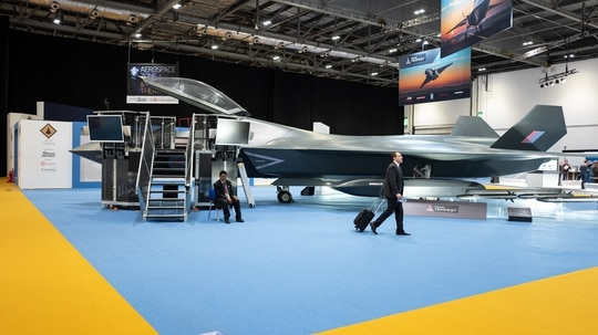 A delegate walks past a model of BAE Systems' Tempest fighter at the DSEI arms fair on Sept. 10, 2019, in London, England. (Jane Garcia/AFP via Getty Images)