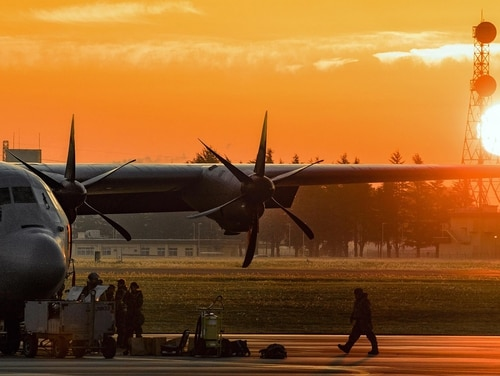 A crew chief assigned to the 374th Aircraft Maintenance Squadron walks by a C-130J from Dyess Air Force Base in Texas. (Yasuo Osakabe/Air Force)