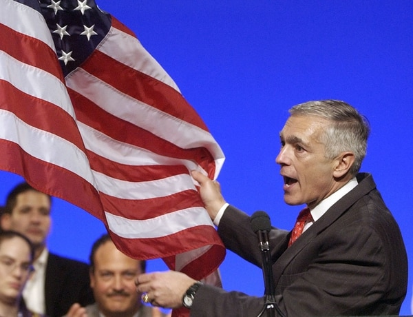 FILE - In this Saturday, Dec. 6, 2003 file photo, presidential candidate Wesley Clark holds a U.S. flag as he speaks to delegates at the Florida Democratic Party convention in Lake Buena Vista, Fla. The commander in chief of U.S. European command and candidate for Democratic presidential nomination in 2003 was the target of 13 phishing emails during April-December 2015 at his Gmail address, according to data from the cybersecurity firm Secureworks. (AP Photo/Scott Martin)