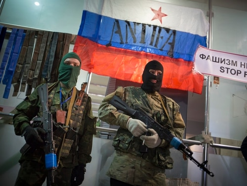 Pro-Russian gunmen guard the Ukrainian regional office of the Security Service in Luhansk, Ukraine, in this 2014 photo. Russian border guards opened fire on three Ukrainian vessels late Sunday, Nov. 25, 2018 in the Kerch Strait near the Russia-occupied Crimean peninsula, raising the prospect of a full-scale military confrontation between the two neighbors. The incident comes on the back of a four-and-a-half year long proxy conflict in eastern Ukraine. (Alexander Zemlianichenko/AP)