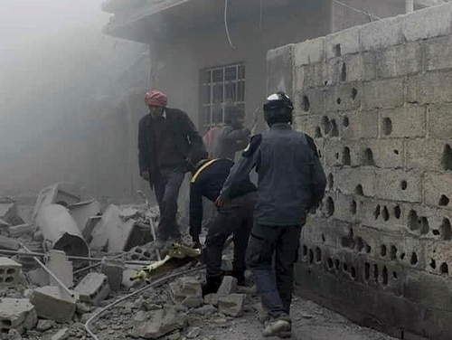 This photo provided by the Syrian Civil Defense White Helmets, which has been authenticated based on its contents and other AP reporting, shows members of the Syrian Civil Defense group and civilians gathering to help survivors from a street attacked by airstrikes and shelling by Syrian government forces in Ghouta, a suburb of Damascus, Syria, Friday, March. 2, 2018. (Syrian Civil Defense White Helmets via AP)