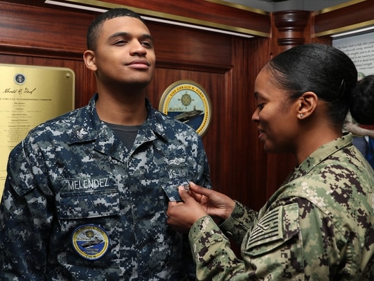 Information Systems Technician 2nd Class Josh Melendez, assigned to the aircraft carrier Gerald R. Ford's combat systems department, receives his Enlisted Aviation Warfare Specialist pin during a Jan. 18 ceremony inside the ship's tribute room. (Mass Communication Specialist 2nd Class Ryan Seelbach/Navy)