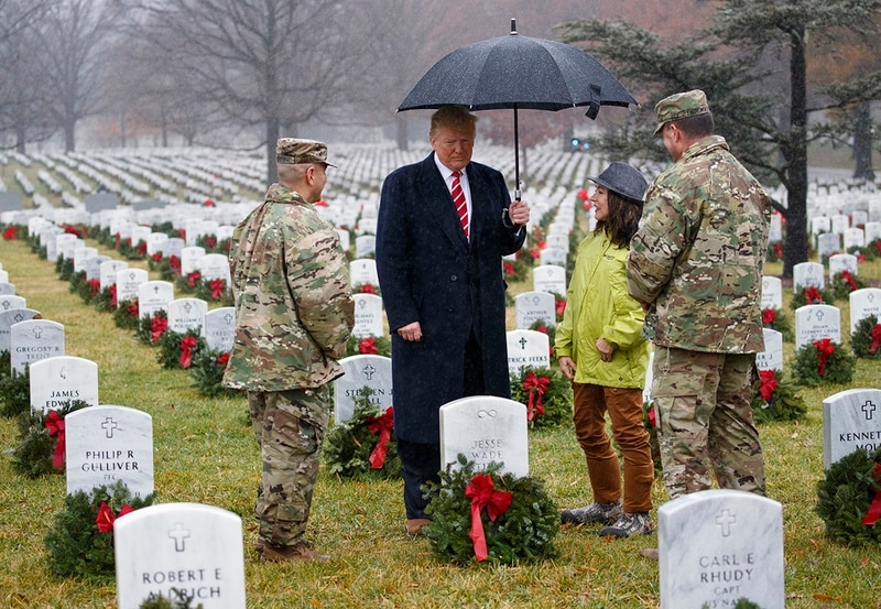 President Donald Trump pauses in the rain among holiday wreaths at graves at Arlington National Cemetery in Arlington, Va., Saturday, Dec. 15, 2018, during Wreaths Across America Day. Wreaths Across America was started in 1992 at Arlington National Cemetery by Maine businessman Morrill Worcester and has expanded to hundreds of veterans' cemeteries and other locations in all 50 states and beyond. (Carolyn Kaster/AP)