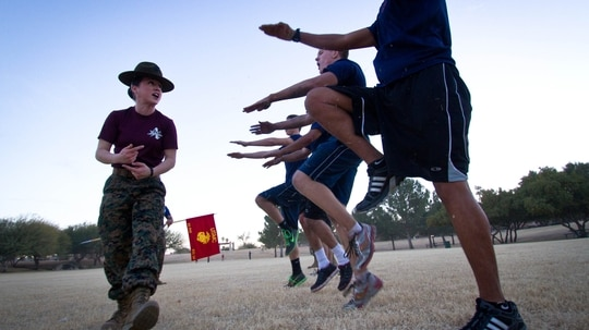 Sgt. Julie Martinez, a drill instructor from 4th Battalion at Marine Corps Recruit Depot Parris Island, South Carolina, instructs Marine Corps Recruiting Substation Chandler enlistees to do high-knees during a physical training exercise in Chandler, Arizona, in 2013. (Cpl. Tyler J. Bolken/Marine Corps)