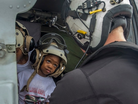 Navy Aircrewman (Helicopter) 2nd Class Logan Parkinson, assigned to Helicopter Sea Combat Squadron 22, prepares a patient's family for evacuation during relief efforts in the wake of Hurricane Maria in St. Croix, U.S. Virgin Islands, Sept. 21. (MC3 Levingston Lewis/Navy)