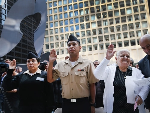 CHICAGO, IL - SEPTEMBER 16: FN Yngrid Castaneda (L), who emigrated from Peru, joins SN Carlos Estrella (C), who emigrated from Mexico and Shireen Shiba (2nd from R), who emigrated from Iraq, in taking the oath of citizenship during a naturalization ceremony in Daley Plaza on September 16, 2014 in Chicago, Castaneda and Estrella recently graduated from U.S. Navy basic training. Seventy people from 25 countries were awarded their U.S. citizenship at the Citizenship Day ceremony. (Photo by Scott Olson/Getty Images)