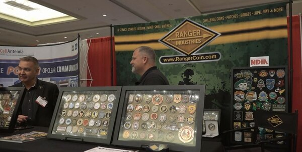 Russ Wilson and Gene Frink display challenge coins their company, Ranger Industries, LLC., produces for clients at the NDIA SO/LIC symposium in Washington, D.C., on March 1.