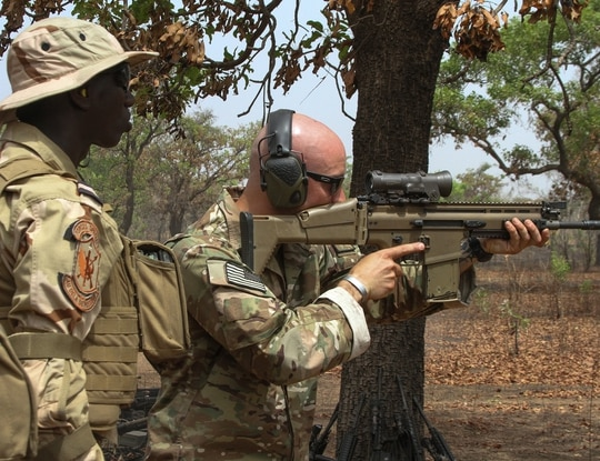 A U.S. Special Forces soldier demonstrates how to fire an Mk 17 sniper rifle for a Senegalese special forces soldier as part of interoperability training during Exercise Flintlock 2019, near Po, Burkina Faso, Feb. 21, 2019. (Sgt. 1st Class Mary S. Katzenberger/Army)