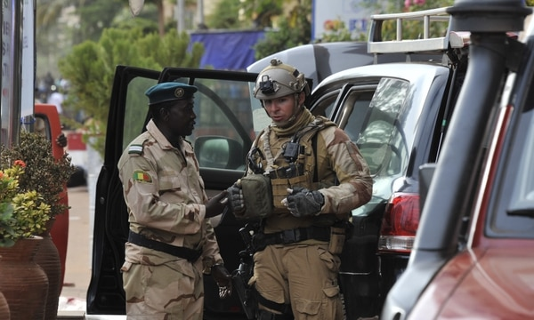 A Malian army officer speaks to a member of an unnamed special operations unit at the entrance to the Radisson Blu hotel in Bamako on Nov. 20, 2015, after the assault of security forces. (Habibou Kouyate/AFP/Getty Images)