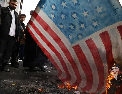 Demonstrators set fire to a rendition of the U.S. flag during a rally in front of the former U.S. Embassy in Tehran, Iran, Monday, Nov. 4, 2019. (Vahid Salemi/AP)