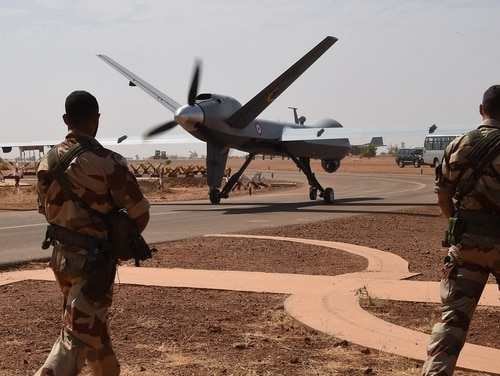 French soldiers stand guard near a Reaper drone about to take off from the Nigerian military airport Diori Hamani in Niamey in January 2015. On the east coast of Africa, the Defense Department has contracted for