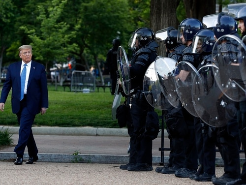 President Donald Trump walks past police in Lafayette Park after he visited outside St. John's Church across from the White House Monday, June 1, 2020, in Washington. Part of the church was set on fire during protests on Sunday night. (Patrick Semansky/AP)