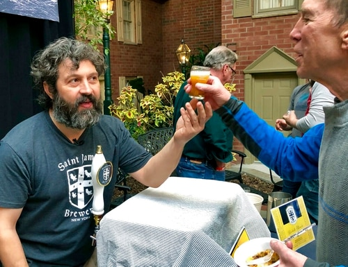 Jamie Adams, left, hands out a sample of his new ale,