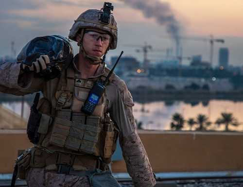 In this Jan. 4, 2020, photo, a U.S. Marine carries a sand bag during the reinforcement of the U.S. embassy compound in Baghdad, Iraq. (Sgt. Kyle C. Talbot/Marine Corps via AP)