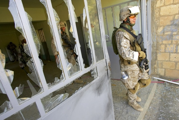 U.S. Marine Staff Sgt. Brian Hamilton of Columbus, Ohio, from Lima Company of the 3rd Battalion, 25th Regiment exits after searching a school where fellow Marines used explosives to blow open the door, shattering the windows, in Parwana, near Haditha, Iraq, Saturday, Aug. 6, 2005. A roadside bomb August 3 nearby killed 14 Marines, many from this platoon, and a civilian interpreter, in the deadliest roadside bombing suffered by American forces in the Iraq war. (AP Photo/Jacob Silberberg)