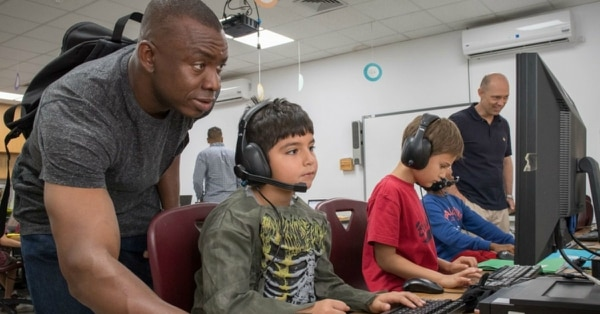 In this October 2018 photo, sailors volunteer at Bahrain School, where a new 'No Body Contact' rule has some parents questioning whether the administration has gone too far. (Mass Communication Specialist 3rd Class Jonathan Clay/Navy)