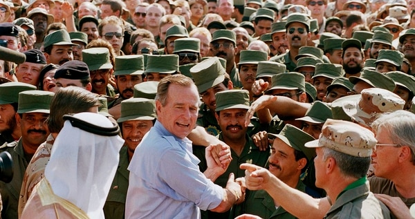 President George H.W. Bush is greeted by Saudi troops and others as he arrives in Dhahran, Saudi Arabia, for a Thanksgiving visit Nov. 22, 1990. (J. Scott Applewhite/AP)