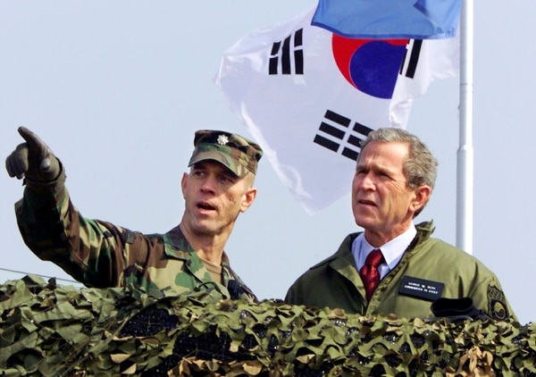 President George W. Bush, right, looks out at North Korea from Observation Point Ouellette in the Demilitarized Zone, the tense military border between the two Koreas, in Panmunjom, Korea, on Feb. 20, 2002. (J. Scott Applewhite/AP)