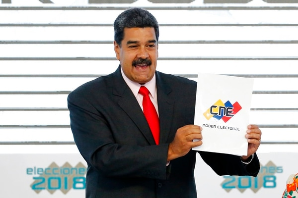 In this May 22, 2018, file photo, Venezuela's President Nicolas Maduro holds up the National Electoral Council certificate declaring him the winner of the presidential election, during a ceremony at CNE headquarters in Caracas, Venezuela. (Ariana Cubillos/AP)