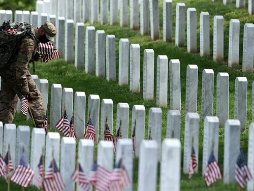 Soldiers from the 3rd Infantry Regiment place U.S. flags in front of every grave site in Arlington National Cemetery on May 21, 2020, in Arlington, Va. (Chip Somodevilla/Getty Images)