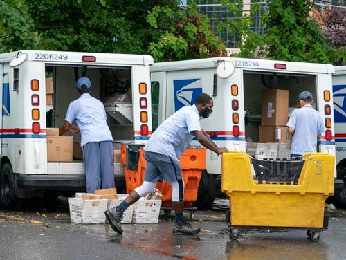In this July 31, 2020, file photo, letter carriers load mail trucks for deliveries at a U.S. Postal Service facility in McLean, Va. (J. Scott Applewhite/AP)