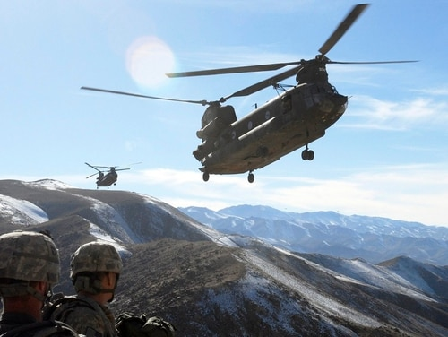 Soldiers with the 101st Airborne Division watch as two Chinook helicopters fly in to take them back to Bagram Air Field, Afghanistan. (Spc. Mary L. Gonzalez/Army)