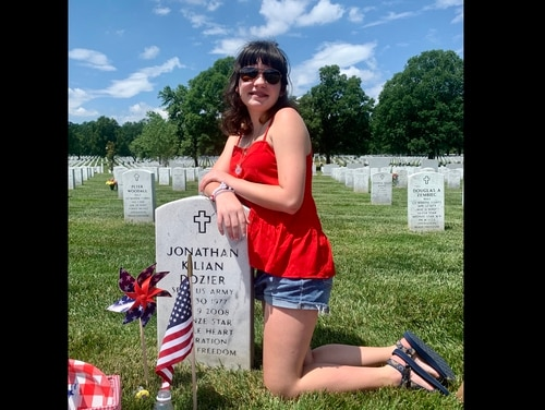 Emma Dozier, daughter of Army Sgt. First 1st Class Jonathan Dozier, poses by his graveside on May 27, 2021. The soldier was killed in a improvised explosive blast in 2008 when Emma was only 13 months old. (Photo courtesy of the Dozier family)
