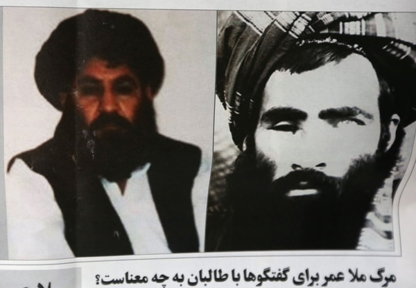 An Afghan newspaper shows pictures of the new leader of the Afghan Taliban, Mullah Akhtar Mohammad Mansoor, left, and Mullah Mohammad Omar, in Kabul, Afghanistan. (AP Photo/Rahmat Gul)