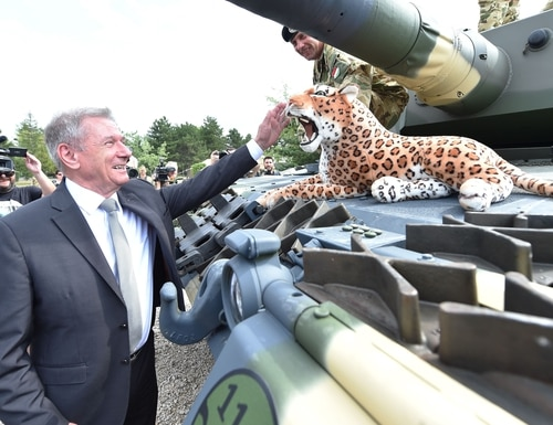 Hungarian Defence Minister Tibor Benko (L) pets a stuffed toy leopard during a handover ceremony of tanks at the army base of Tata, Hungary, on July 24, 2020. (Photo by Attila Kisbenedek/AFP via Getty Images)