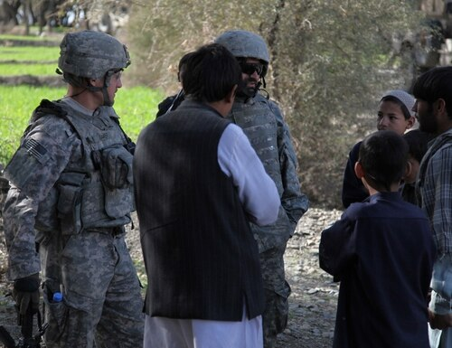A group of local Afghan villagers speak to an interpreter, greeting U.S. Army soldiers. (U.S. Army photo by Spc. Victor Egorov)