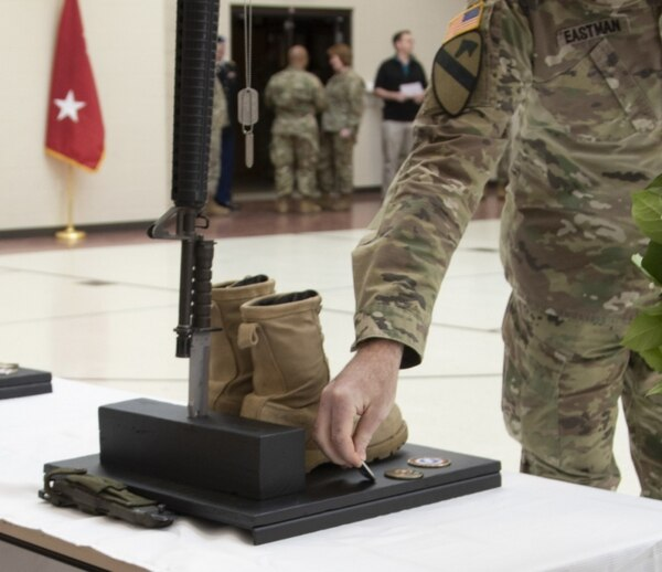 Sgt. Maj. Ross Eastman of the 1st Theater Sustainment Command places a command coin in honor of Sgt. Holli Bolinski at a memorial service March 16.