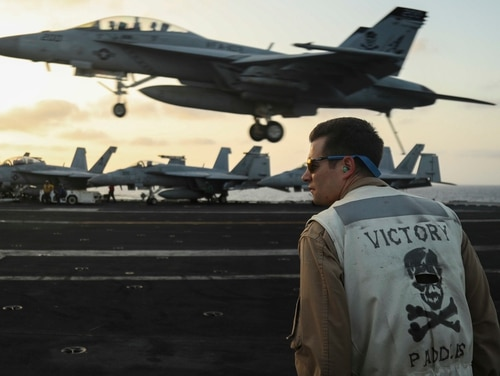 Lt. Nicholas Yerkes, a landing signals officer on board the aircraft carrier Abraham Lincoln, stands watch as an F/A-18F Super Hornet from the Jolly Rogers of Strike Fighter Squadron 103 land on the flight deck. (Mass Communication Specialist 3rd Class Jeff Sherman/Navy)