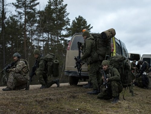 U.S. Army Special Forces and Lithuanian National Defence Volunteers Forces provide security and ready equipment in preparation for a training mission. (Lt. Benjamin Haulenbeek/Army)