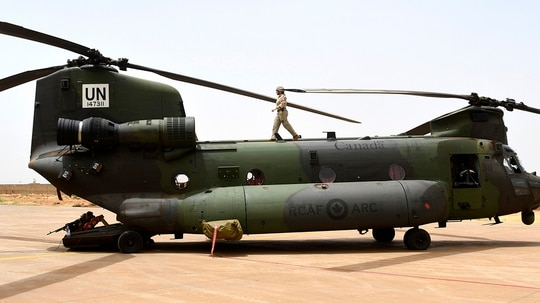 A Canadian United Nations pilot walks on top of a Chinook helicopter at a base in Gao on August 1, 2018, during the United Nations Multidimensional Integrated Stabilization Mission in Mali (MINUSMA) operation.(SEYLLOU/AFP/Getty Images)