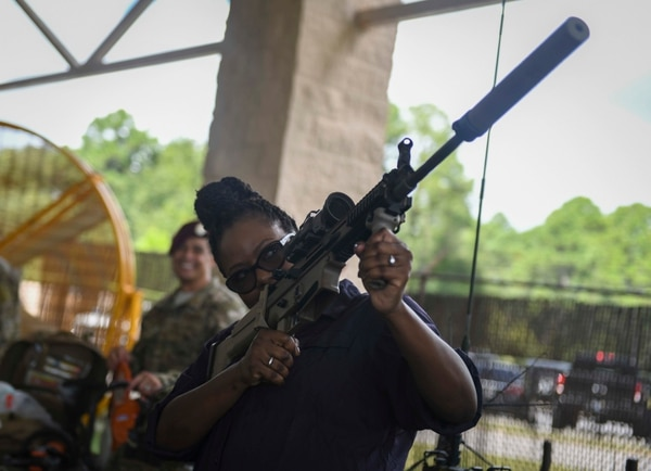 Wendy Calhoun, a producer and writer, holds an FN SCAR rifle during an Air Force Special Operations Command immersion at Hurlburt Field, Florida. (Airman 1st Class Dennis Spain/Air Force)