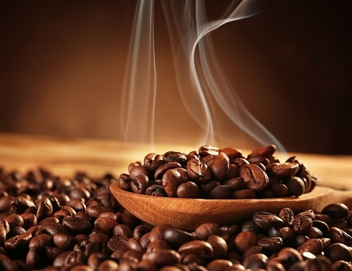 Wooden spoon with roasted coffee beans on blurred background