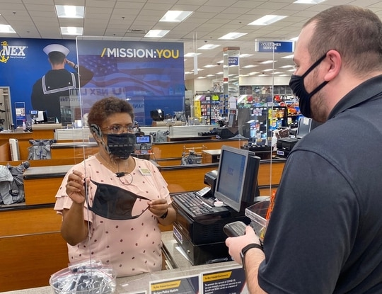 Kym-Tol Alston sells a cloth face covering to a customer in the Navy Exchange at Little Creek, Va., on May 13. (Kristine Sturkie/NEXCOM)