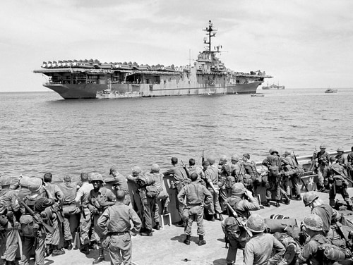 Troops from the First Cavalry Air Mobile Division watch the carrier USS Boxer after arrival at Qui Nhon, Vietnam, on Sept. 12, 1965. On Tuesday, Department of Justice officials announced they will not appeal a court ruling that will award presumptive disability benefits to thousands of so-called