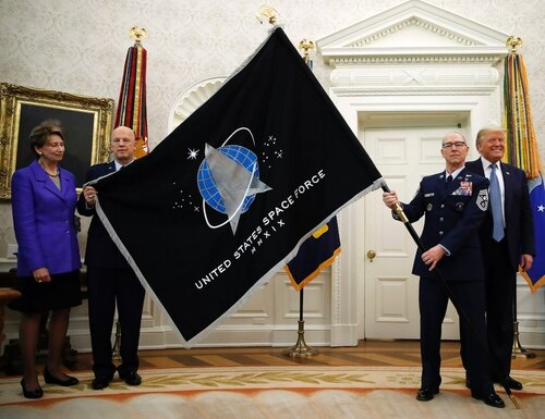 Chief Master Sgt. Roger Towberman, near right, unfurls the new Space Force Flag in a White House ceremony May 15 with, from left, then-Air Force Secretary Barbara Barrett, Chief of Space Operations Gen. Jay Raymond, and then-President Trump. Towberman will be known as the chief master sergeant of the Space Force under the service's new rank structure, unveiled Jan. 29. (Alex Brandon/AP)