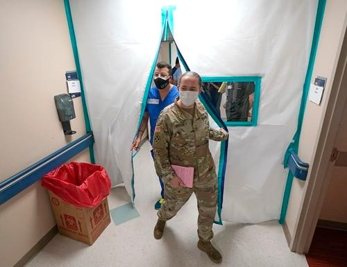 Urban Augmentation Medical Task Force members Army Maj. Katy Bessler, right, and Infectious Disease Physician Maj. Gadiel Alvarado enter a wing at United Memorial Medical Center, Thursday, July 16, 2020, in Houston. (David J. Phillip/AP)