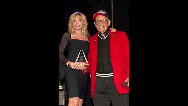 In this Sept. 11, 2013, file photo, actress Loni Anderson, left, receives the Millie Taylor award from Lt. Col. Bob Friend, a Tuskegee Airman, during the 2nd Annual Heroes Helping Heroes Benefit Concert at The House of Blues, in Los Angeles. World War II pilot Friend, one of the last original members of the famed all-black Tuskegee Airmen, has died at the age of 99. (Paul A. Hebert/Invision/AP)