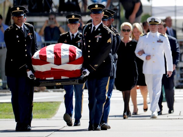 Military personal carry the casket of Sen. John McCain, R-Ariz., into the Capitol rotunda for a memorial service as Cindy McCain and her son Jack McCain follow, Wednesday, Aug. 29, 2018, at the Capitol in Phoenix. (AP Photo/Matt York)