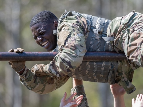 Spc. Tradale Bryant, of the 55th Signal Company, pulls himself over a high bar during the obstacle course portion of the 2018 SPC Hilda I. Clayton Best Combat Camera Competition at Marine Corps Base Quantico, Virginia, on May 1. (Staff Sgt. Pablo N. Piedra/Army)