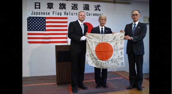 U.S. Air Force Senior Master Sgt. William Armstrong (left) hands a Japanese Good Luck Flag to Michio Miki (middle) and Hideo Ito, Masashi Ito's nephews, during a flag return ceremony in Takasaki, Japan, Feb. 14. (Obon Society)
