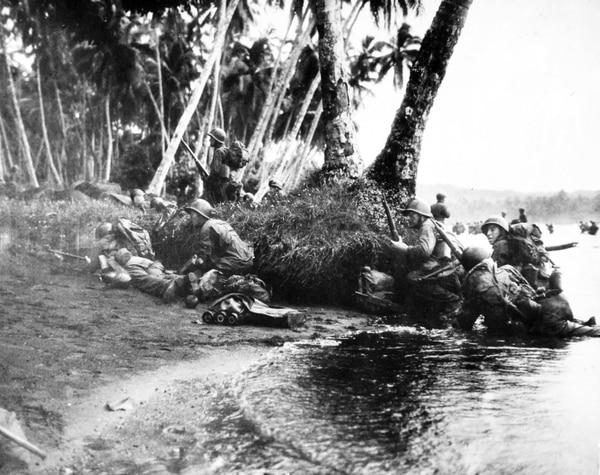 Attacking at dawn in a heavy rainstorm, the first Americans ashore on Rendova Island in 1943 huddled behind tree trunks and any other cover they could find. (Navy)