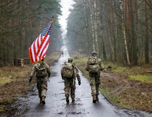 American soldiers ruck march with the flag on March 6, 2020, during the 1st annual Bataan Memorial Death March on Powidz Air Base in Powidz, Poland. (Master Sgt. Ryan Matson/Army Reserve)